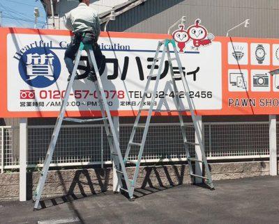 新店舗の新しい看板を取り付け工事中の風景